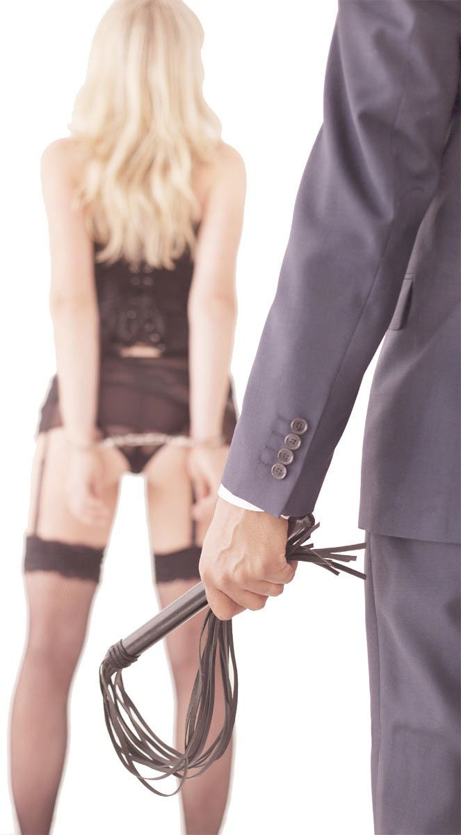 A woman wearing lingerie and handcuffs and a man in suit holding a wip.